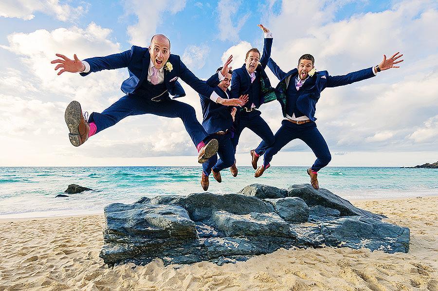 Groomsmen jumping for joy at beach wedding