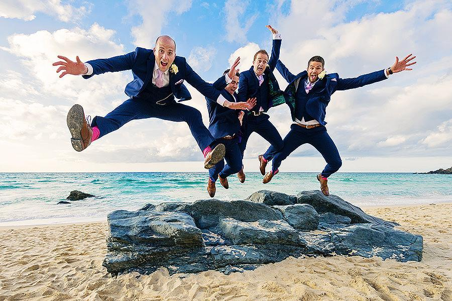 Groomsmen jumping for joy at beach wedding