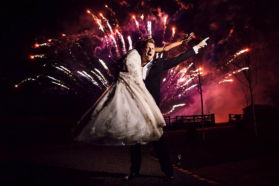 Bride and Groom fire-mans lift  in front of fireworks
