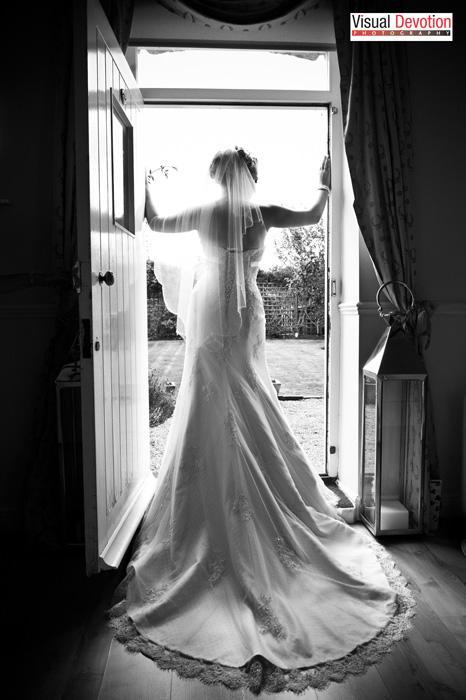 wedding photography - bride looks through window