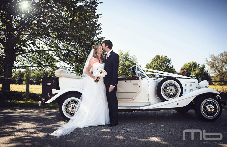 wedding photo Bride +Groom with classic wedding car